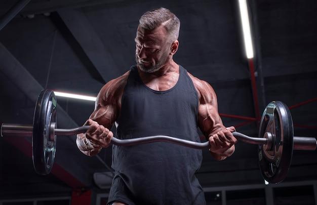 ジムでバーベルを持ち上げる強力なアスリートの画像。上腕二頭筋のポンピング。フィットネスとボディービルのコンセプト。ミクストメディア