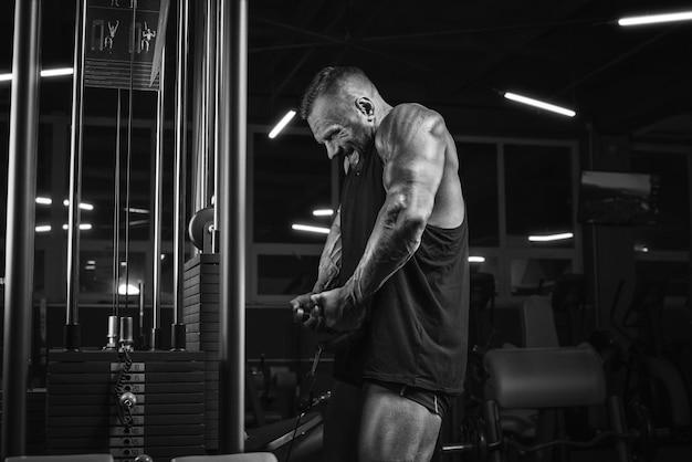 ジムでウェイトトレーニングをしている強力なアスリートの画像。ショルダーポンピング。フィットネスとボディービルのコンセプト。ミクストメディア
