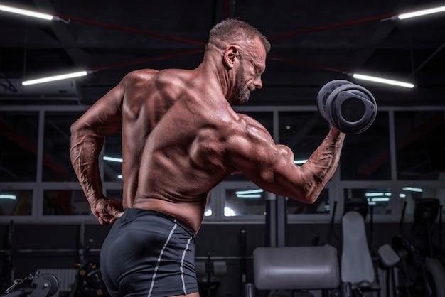 ジムでダンベルを使って上腕二頭筋をポンピングする強力なアスリートの画像。フィットネスとボディービルのコンセプト。ミクストメディア