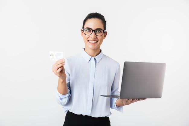신용 카드를 들고 노트북 컴퓨터를 사용 하여 흰 벽 위에 절연 예쁜 비즈니스 여자의 이미지.