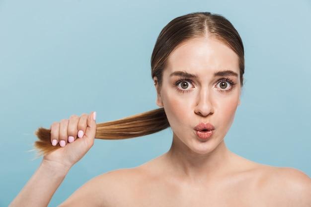 Изображение довольно потрясенной взволнованной молодой женщины, позирующей изолированной над синей стеной, касающейся волос.