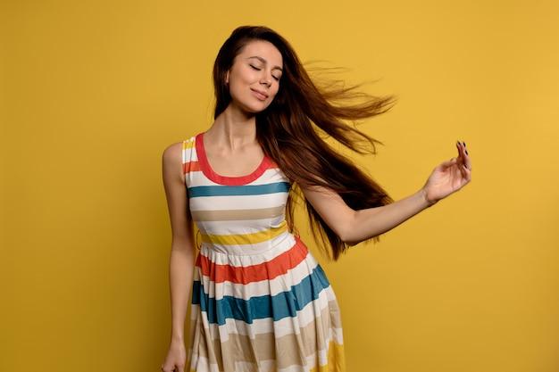Изображение довольно улыбающейся молодой женщины в ярком летнем платье, изолированной над желтой стеной. модный портрет красивой девушки, позирующей, развлекаясь над красочной стеной