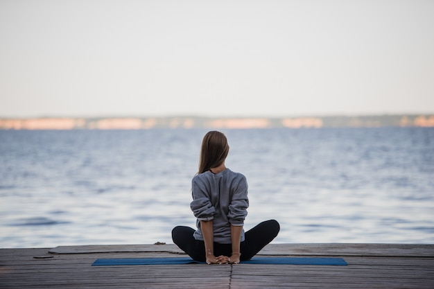 湖でヨガをやっているきれいな女性の画像