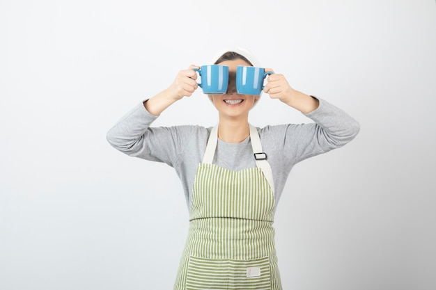 Изображение красивой молодой женщины в фартуке, закрывающей глаза двумя голубыми чашками