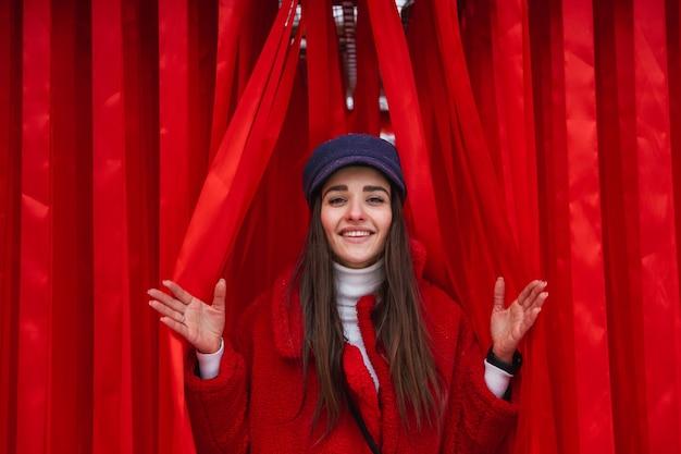 Изображение красивой молодой женщины выглядывает между красной занавеской.