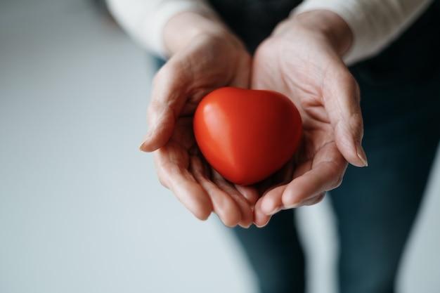 女性の手のひらに赤いハートの画像