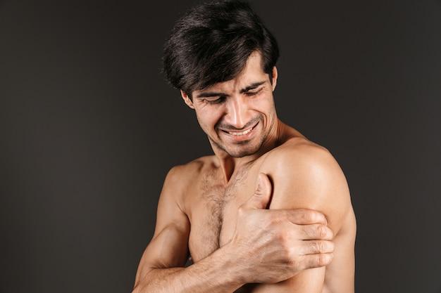 Изображение грустного недовольного молодого человека с изолированным представлением боли в руке.