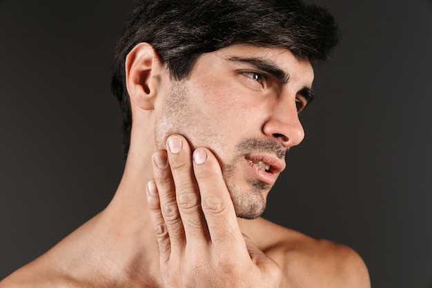 Изображение грустного недовольного молодого человека с зубной болью позирует изолированы.