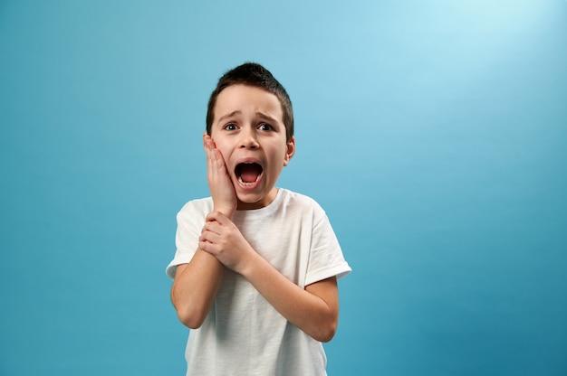 파란색 표면에 정면으로 포즈를 취하는 동안 그의 뺨을 덮고 고통에 비명을 지르는 남학생의 이미지