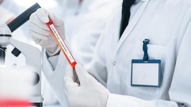 Изображение ученого, смотрящего на пробирку с тестом