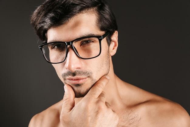 Изображение серьезного сконцентрированного красивого молодого человека, изолированного в очках.