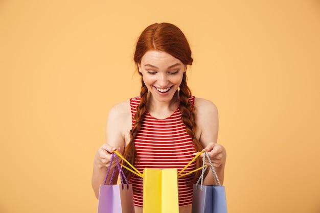 Изображение потрясенной молодой красивой рыжей женщины, позирующей изолированной над желтой стеной, держащей хозяйственные сумки.