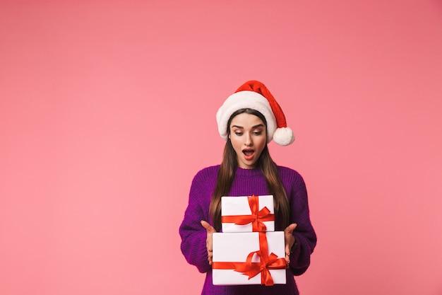 クリスマスの帽子をかぶったピンクの保持ギフトボックスの上に孤立してポーズをとってショックを受けた若い感情的な女性の画像。