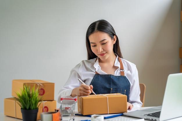 집으로 배달할 주소를 적기 위해 펜과 소포 상자를 들고 있는 소기업 소유자의 이미지.