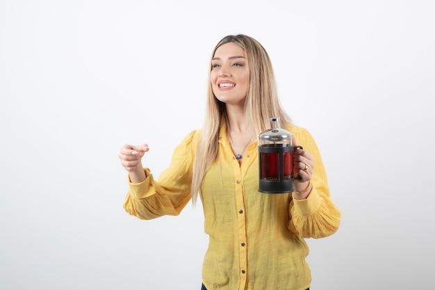 Изображение улыбающейся модели красивой женщины, держащей чайник.