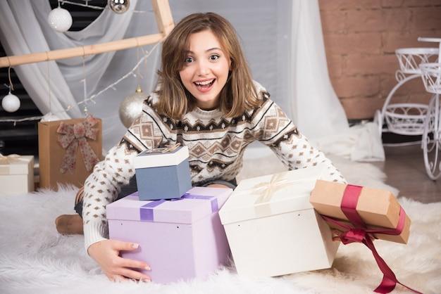 거실에서 크리스마스 선물을 들고 웃는 여자의 이미지.