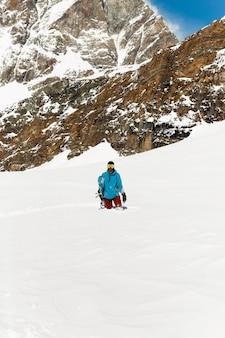 Изображение сноуборда, стоящего в снегу, на фоне высоких гор