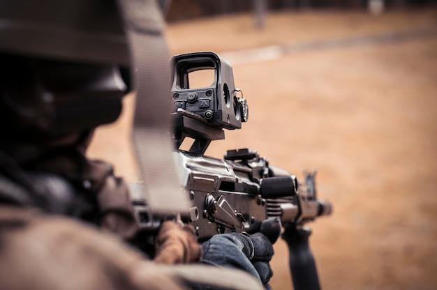 콜리메이터 조준기를 조준하는 군인의 이미지. 군사 충돌의 개념입니다. 혼합 매체