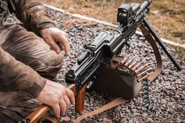 중기관총을 장비하는 군인의 이미지. 군사 충돌의 개념입니다. 혼합 매체