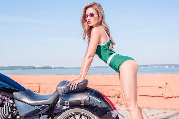 거대한 오토바이 옆에 서 있는 녹색 비키니를 입은 멋진 세련된 금발의 이미지. 모터스포츠, 관광, 패션 스타일의 개념. 혼합 매체