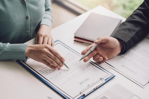 Изображение руки женщины, держащей ручку, читая резюме с контрактными документами в офисе.