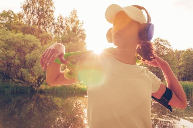 Изображение женщины в кепке и наушниках со скейтбордом. закат в парке. концепция отпуска. смешанная техника