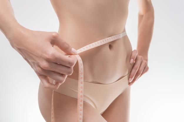Изображение женского живота, обмотанного сантиметровой лентой. медицинская концепция. антицеллюлитный. смешанная техника
