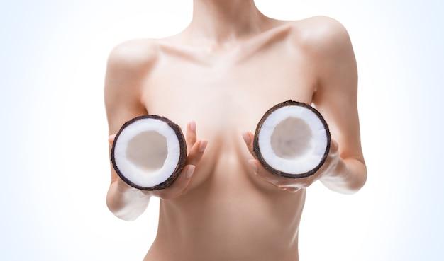 Изображение груди женщины, покрытой кокосом. концепция пластической хирургии. маммология. силиконовые имплантаты. смешанная техника