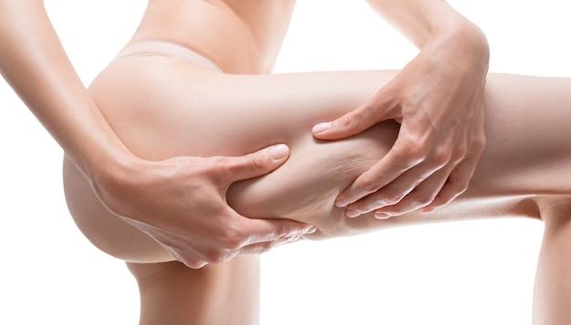 太ももの皮膚を圧迫する女性の画像。化粧品のコンセプト。ミクストメディア