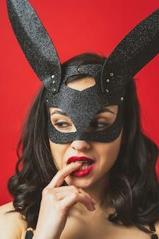 セクシーなウサギのマスクを身に着けて、赤い色の背景にポーズをとる女性の画像