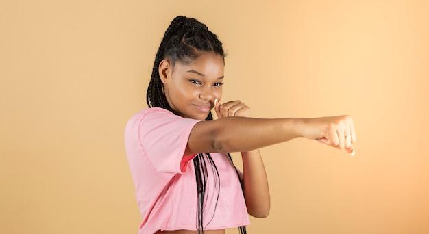若いアフリカのボクサーの画像はパンチ、強い女性、黄色の背景を投げる