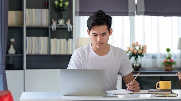 Изображение молодого азиатского человека, работающего дома, используя ноутбук и делая заметки на кофе за столом.