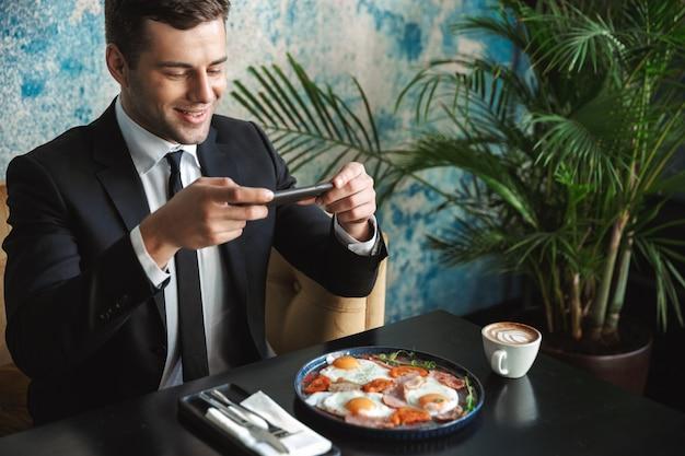 カフェに座っている青年実業家の画像は、携帯電話で食べ物の写真を撮ります。