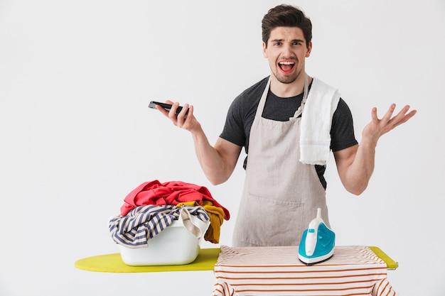 Изображение молодого сбитого с толку недовольного домочадца с утюгом возле одежды, изолированной над белой стеной, с помощью мобильного телефона.