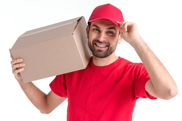 Изображение молодой доставщик держит коробку и шапку