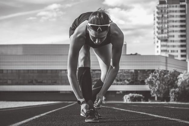若い女性ランナーの画像は、スタジアムのトラックで彼女の靴をひもで締めます。スポーツの概念。