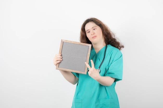 녹색 승리 기호를 표시하는 프레임으로 균일 한 젊은 여자의 이미지.