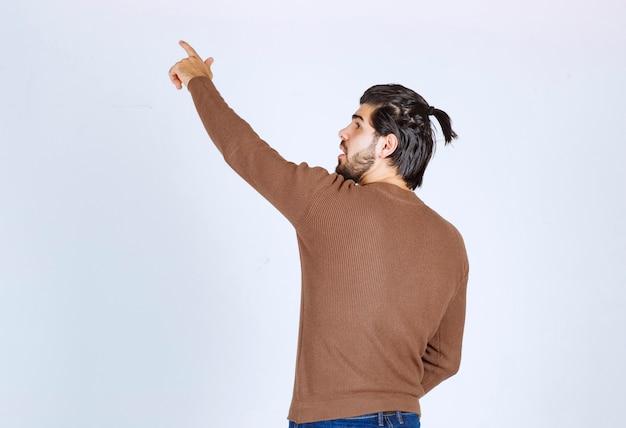 서서 손가락으로 가리키는 젊은 잘 생긴 남자 모델의 이미지. 고품질 사진