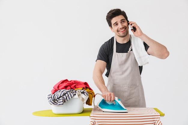 휴대 전화로 얘기 하는 흰 벽 위에 절연 옷 근처에 철으로 젊은 행복 한 주부의 이미지.