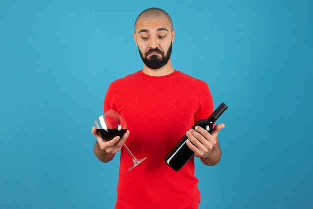 Изображение модели молодого человека в красной футболке, держащей бутылку вина со стеклом.