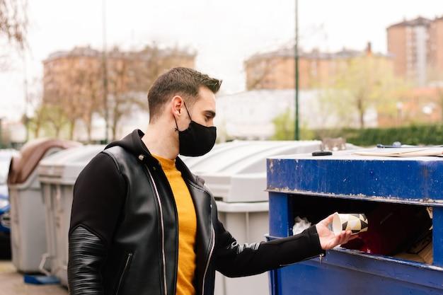 Изображение молодого человека, бросающего бумажный стаканчик в мусорную корзину, экологическая концепция, всемирный день окружающей среды