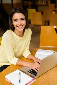 읽기 공부 하 고 랩톱 컴퓨터를 사용 하여 숙제를 하 고 도서관에서 젊은 학생 행복 한 여자의 이미지.