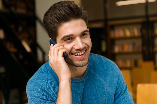 携帯電話で話すことを勉強している宿題をしている図書館の若い学生男性の画像。