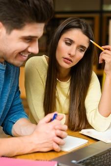 읽기 공부 하 고 랩톱 컴퓨터를 사용 하여 숙제를 하 고 도서관에서 젊은 학생 친구 커플의 이미지.