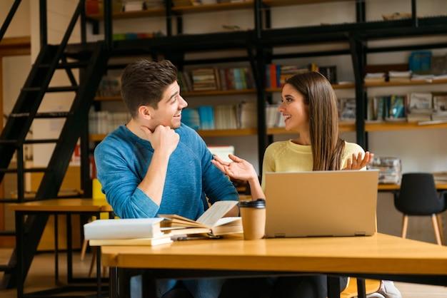 読書を勉強し、ラップトップコンピューターを使用して宿題をしている図書館の若い学生の友人のカップルの画像。
