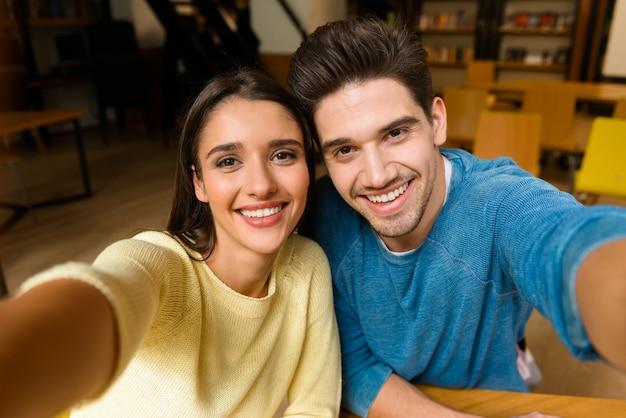 宿題を勉強している図書館で若い学生の友人のカップルが自分撮りをする画像