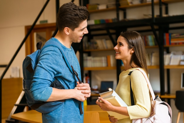 図書館で若い学生の友人のカップルがお互いに話していることを勉強している画像。