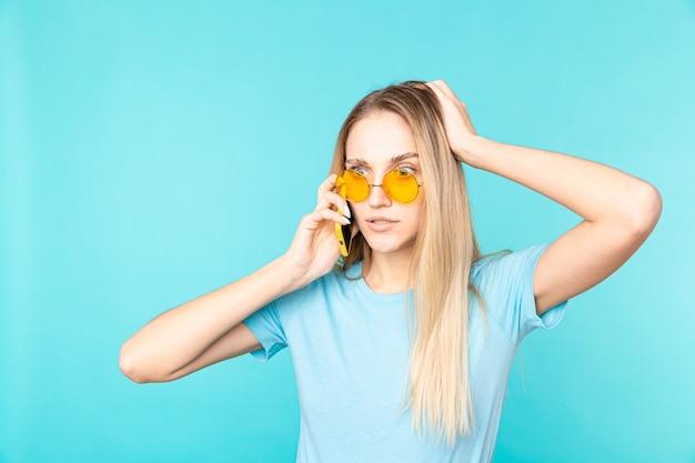 Изображение молодой женщины, держащей смартфон и выражающей изумление, изолированное на синем