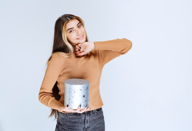 Изображение модели молодой женщины в коричневом свитере стоя и позируя с подарочной коробкой.