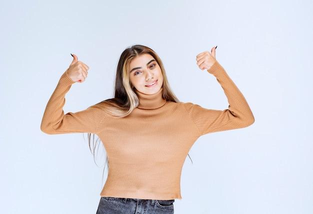서서 엄지손가락을 보여주는 갈색 스웨터를 입은 젊은 여성 모델의 이미지.